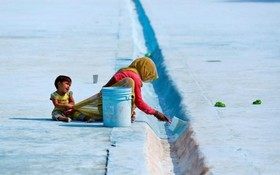 یک زن کارگر هندی در حال کار در دهلی همراه کودکش