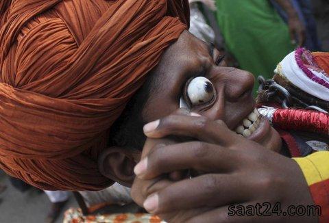 یک روحانی فرقه خاصی در حال انجام یک نمایش در جریان یک مراسم مذهبی سالانه در هند