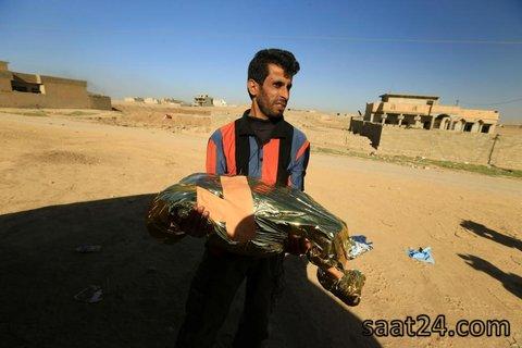 یک ساکن موصل دخترش را که در حملات داعش کشته شده برای دفن می برد
