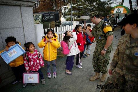 یک سرباز آمریکایی در بخش کره جنوبی در مز این کشور با کره شمالی در حال بازی با یک کودک