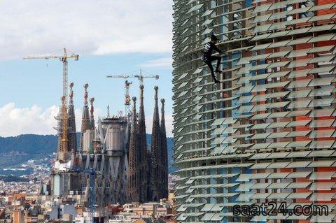 صخره نورد فرانسوی آلن روبرت که  به مرد انکبوتی فرانسوی مشهور است در اسپانیا در حال بالارفتن از یک ساختمان سی و هشت طبقه در حالی که کلیسای مشهور ساگرادا در زمینه دیده می شود