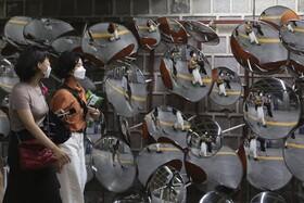مسافران مترو در ایستگاهی در سئول کره جنوبی در مقابل دیواری از آینه ها