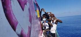 مهاجرانی که در دریای مدیترانه توسط کشتی بنکسی هنرمند گرافیتی انگلیسی نجات داده شده اند