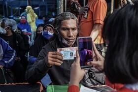 صف دریافت کمک های دولتی در اندونزی که مامور برای ثبت مشخصات افراد از آنان عکس می گیرد