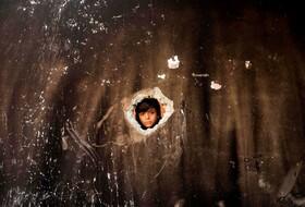 کودکی فلسطینی در غزه به خانه ای نگاه می کند که دوکودک در آن در اثر آتش سوزی جانباختند